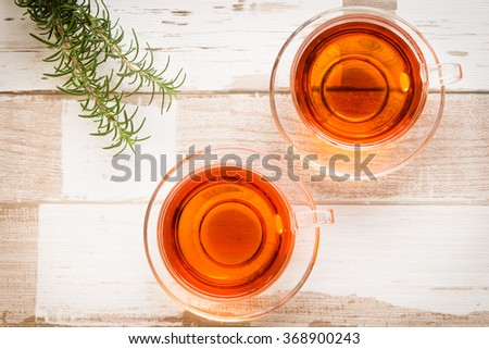 Healthy food arrangement with two glass cups of herbal or black tea and rosemary leaves on a rustic wooden table. View from above/top.