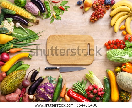 Healthy food background and Copy space / studio photography of wooden board surrounded by fresh vegetables on wooden table. Top view