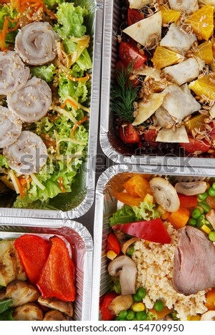 Healthy food background. Take away of natural organic food in foil boxes. Fitness nutrition, meat and vegetable salads. Top view, flat lay.