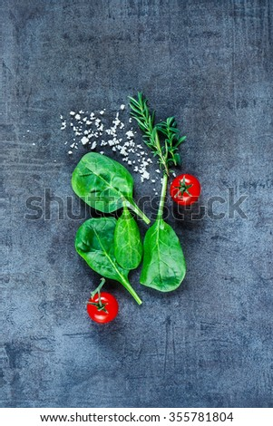 Healthy food background with fresh vegetarian ingredients (spinach, tomatoes, grey salt and herbs) on dark vintage table, top view. Vegan or diet nutrition concept.  - stock photo