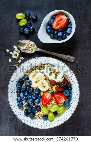 Healthy food background with plate of oat flakes, berries with yogurt and seeds for tasty breakfast on dark vintage board -  Diet, Detox, Clean Eating or Vegetarian concept. - stock photo