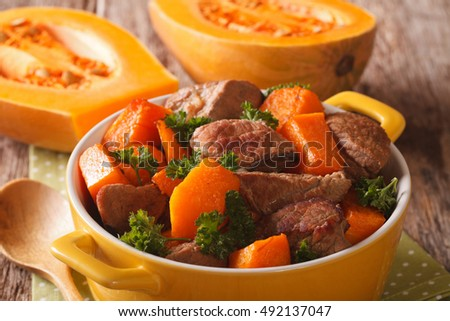 Healthy food: Beef stew with pumpkin and spices close up in a yellow pot on the table. horizontal