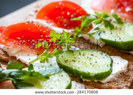 Healthy food, breakfast sandwiches. Finnish rye crisp bread, soft cheese, cucumber, tomato, parsley and black pepper - stock photo