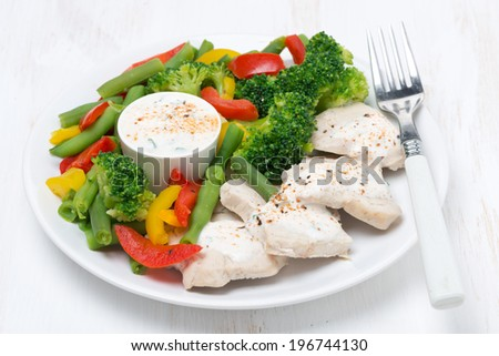 healthy food - chicken, steamed vegetables and yoghurt sauce on a plate, close-up