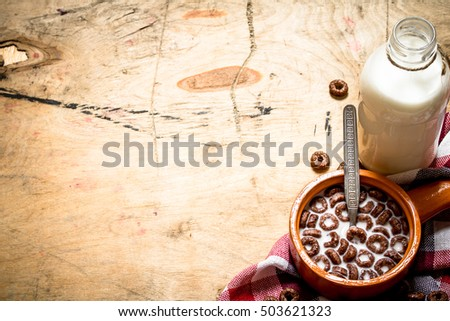 Healthy food. Chocolate cereal with milk. On wooden background.