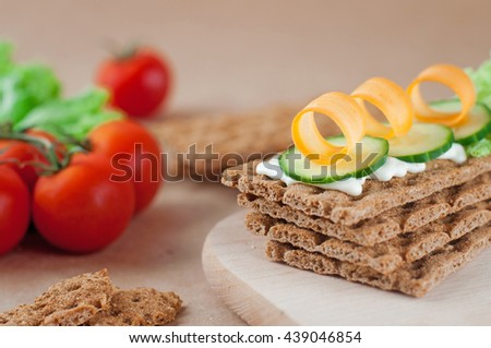 Healthy food concept: Close up of crispbreads with soft cheese, cucumber and carrot. Selective focus on vegetables. - stock photo