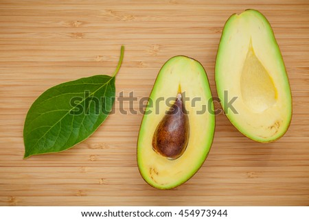 Healthy food concept. Closeup ripe avocado with avocado leaves on wooden background. Halved organic avocado with core on wooden background.  Top view with copy space. - stock photo