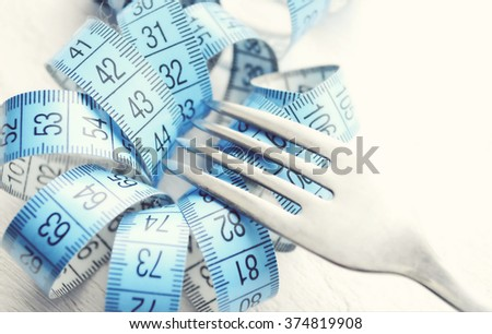Healthy food concept. Fork, knife and tape measure on wooden table. Top view with copy space.fork and measuring tape on a plate