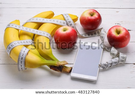 Healthy food concept, fresh bananas and apples on a wooden table. Measuring tape and a telephone, a sports diet.