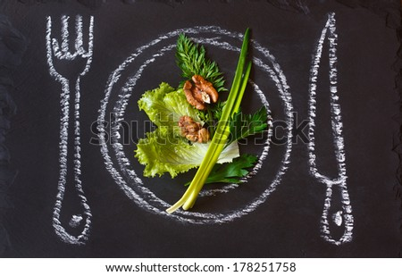 Healthy food concept. Fresh organic green salad on a chalk painted plate. - stock photo