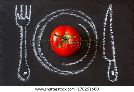 Healthy food concept. Fresh organic tomato on a chalk painted plate. - stock photo