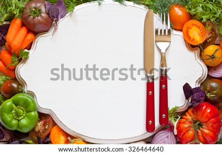 Healthy food concept. Fresh young organic vegetables around serving board from above. - stock photo