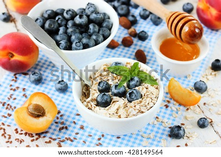 Healthy food concept - oatmeal granola with berries, fruits, honey and flax seeds selective focus - stock photo