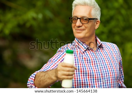 Healthy food concept. Portrait of a mature (old) man in trendy casual shirt and glasses posing in the park and holding a bottle with milk. Sunny summer day. Copy-space. Outdoor shot - stock photo