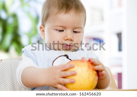 Healthy food concept: Sweet baby boy looking at apple while holding it in his hands. - stock photo