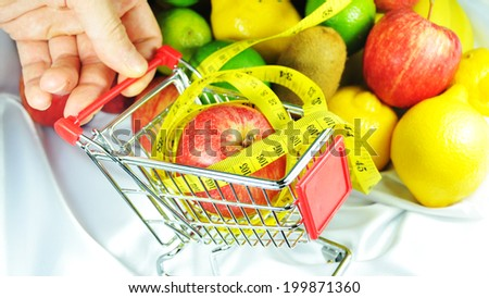 Healthy food concept with shopping trolley and fruits - stock photo