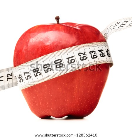 healthy food. Delicious apple with measuring tape on red background - stock photo
