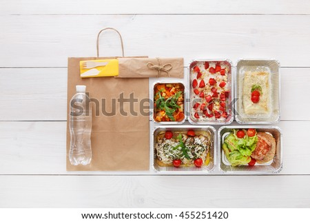 Healthy food delivery, daily meals and snacks. Diet nutrition, vegetables, berry oatmeal, meat and water bottle in foil boxes and brown paper package. Top view, flat lay at white wood with copy space - stock photo