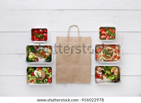 Healthy food delivery, daily meals and snacks. Diet nutrition, vegetables, meat and fruits in foil boxes and brown paper package. Top view, flat lay at white wood with copy space - stock photo