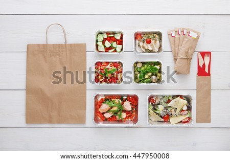 Healthy food delivery. Take away of natural organic low carb diet. Fitness nutrition in foil boxes, water bottle, cutlery and brown paper package with copy space. Top view, flat lay at white wood - stock photo