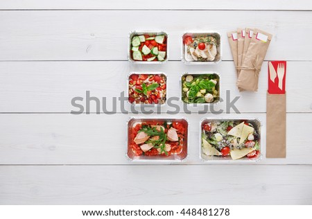 Healthy food delivery. Take away of natural organic low carb diet. Fitness nutrition in foil boxes, cutlery in brown paper package. Top view, flat lay with copy space at white wood - stock photo
