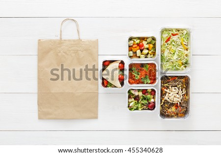 Healthy food delivery. Take away of natural organic low carb diet. Fitness nutrition in foil boxes, cutlery and brown paper package bag. Top view, flat lay with copy space at white wood - stock photo
