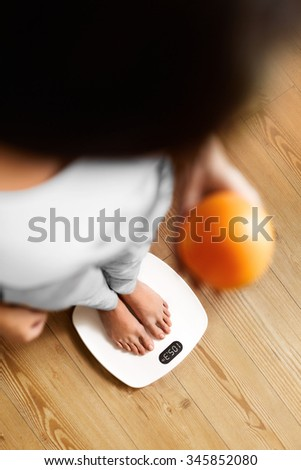 Healthy Food Eating. Female Feet Standing On Scale. Woman Measuring Body Weight On Weighing Scale, Holding Orange In A Hand. Weight Loss. Diet And Dieting, Exercising. Healthy Lifestyle. - stock photo