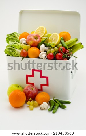 Healthy food. First aid box filled with fresh fruits and vegetables on white background. - stock photo