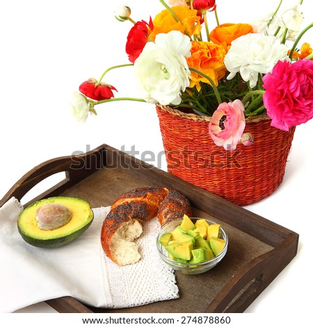 Healthy food for breakfast ( bread with fresh avocado fruit) served on a wood tray and flowers basket. Isolated on a white background. Selective focus - stock photo