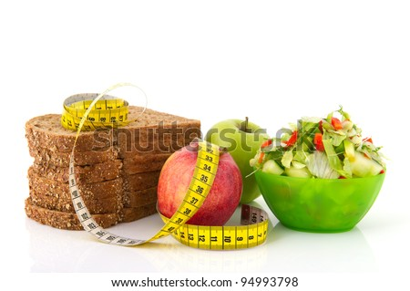 Healthy food for diet as bread fruit and vegetables with measurement tape - stock photo