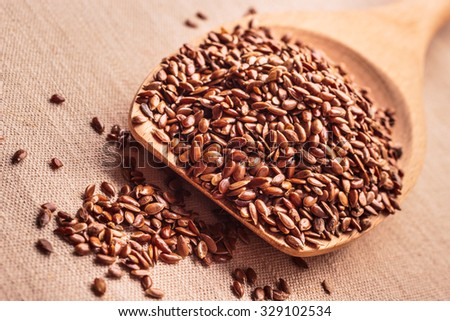 Healthy food for preventing heart diseases and overweight. Flax seeds linseed on wooden spoon burlap background