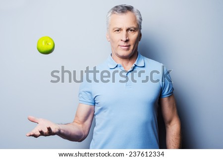 Healthy food for success. Confident senior man in casual throwing a green apple up and smiling while standing against grey background - stock photo