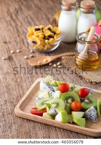 Healthy Food ,fruit salad ,kiwi ,dragon fruit ,apple and tomato with corn flake ,milk and honey on wooden table