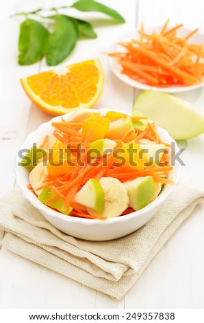 Healthy food. Fruit salad with carrots, apples, bananas and orange slices - stock photo
