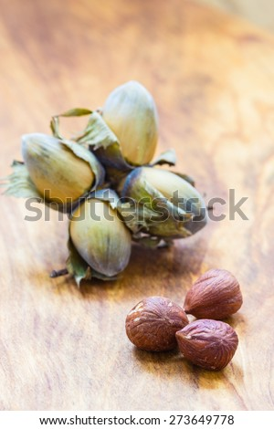 Healthy food full of fatty acids, organic nutrition. Hazelnuts  kernel and cluster filbert nuts in hard shell on rustic old wooden table. - stock photo