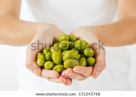 Healthy food green olive in human hands. - stock photo