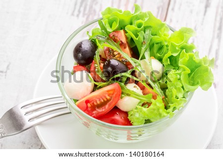 healthy food - green salad with mozzarella, arugula and tomatoes in a bowl