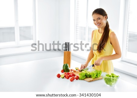 Healthy Food. Happy Smiling Young Woman Preparing Vegetarian Dinner, Cutting Organic Vegetables, Cooking Salad With Knife In Kitchen. Healthy Lifestyle And Eating. Diet, Dieting Concept. Nutrition. - stock photo