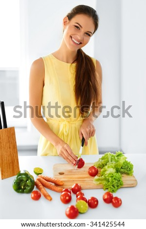 Healthy Food. Happy Smiling Young Woman Preparing Vegetarian Dinner, Cutting Vegetables, Cooking Salad With Knife In Kitchen. Healthy Lifestyle And Eating. Diet, Dieting Concept. Nutrition