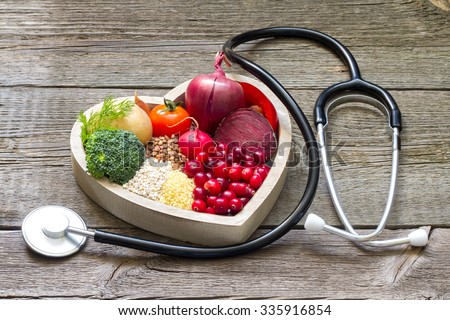 Healthy food in heart and cholesterol diet concept on vintage boards