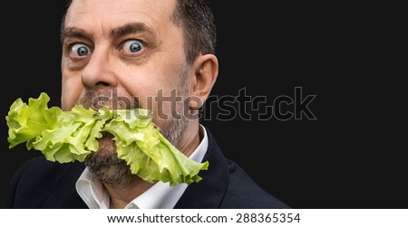 Healthy food. Man eating lettuce on dark background with copy-space