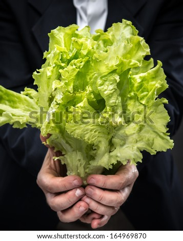 Healthy food. Man holding and eating lettuce