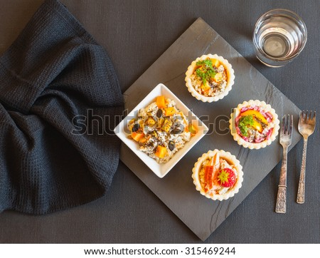 Healthy food. Mini tarts with various salads with Chia seeds. Quinoa salad with raw pumpkin, carrots and soy bean, Chia, pumpkin, sunflower and pine seeds, coconut sauce. - stock photo