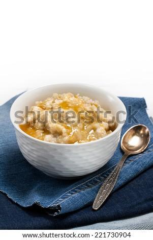 Healthy food - oat bran porridge and honey - stock photo