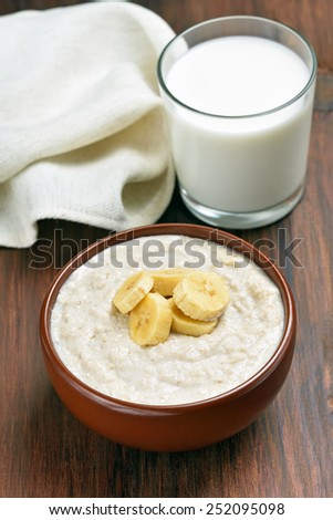 Healthy food. Oatmeal porridge with banana slices and glass of milk on wooden table - stock photo