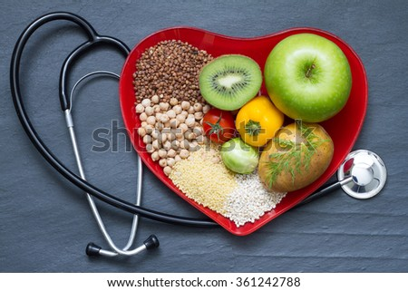 Healthy food on red heart plate cholesterol diet concept - stock photo