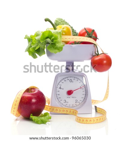 Healthy food on weights and measuring tape isolated on white - stock photo