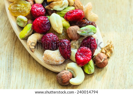 Healthy food organic nutrition. Closeup different varieties mix of dried fruits and nuts on wooden spoon. - stock photo