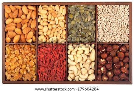 Healthy food organic nutrition.Wooden box full of raw seeds and nuts isolated on white background  - stock photo