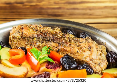 Healthy food, stewed pork meat with various colorful vegetables in pan on wooden background, selective focus, space for text. - stock photo